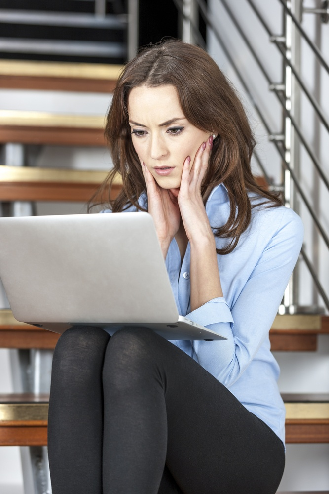 Young woman using a laptop computer looking concerned and worried.jpeg