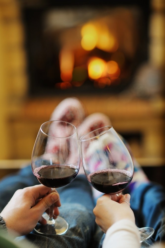 happy Young romantic couple sitting on sofa in front of fireplace at winter season in home.jpeg